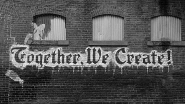 "Black and white image of graffiti on a wall. Graffiti says ""together, we create"""