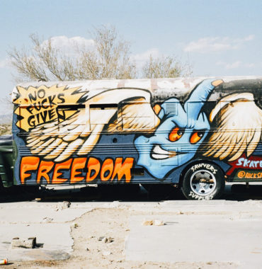 Old bus with graffiti flying middle finger hand and the word 'freedom'