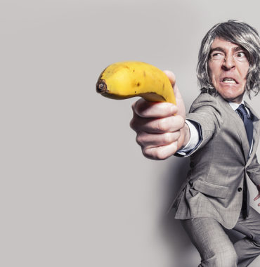 Man using banana like a gun