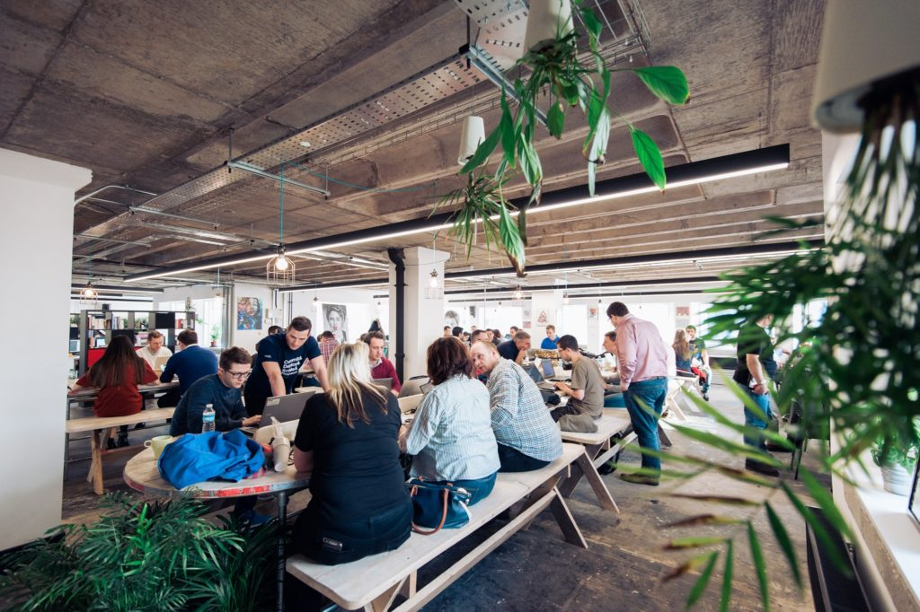 Photograph of the coworking space at Launch 22 - rows of desks and benches with people sat working at them.