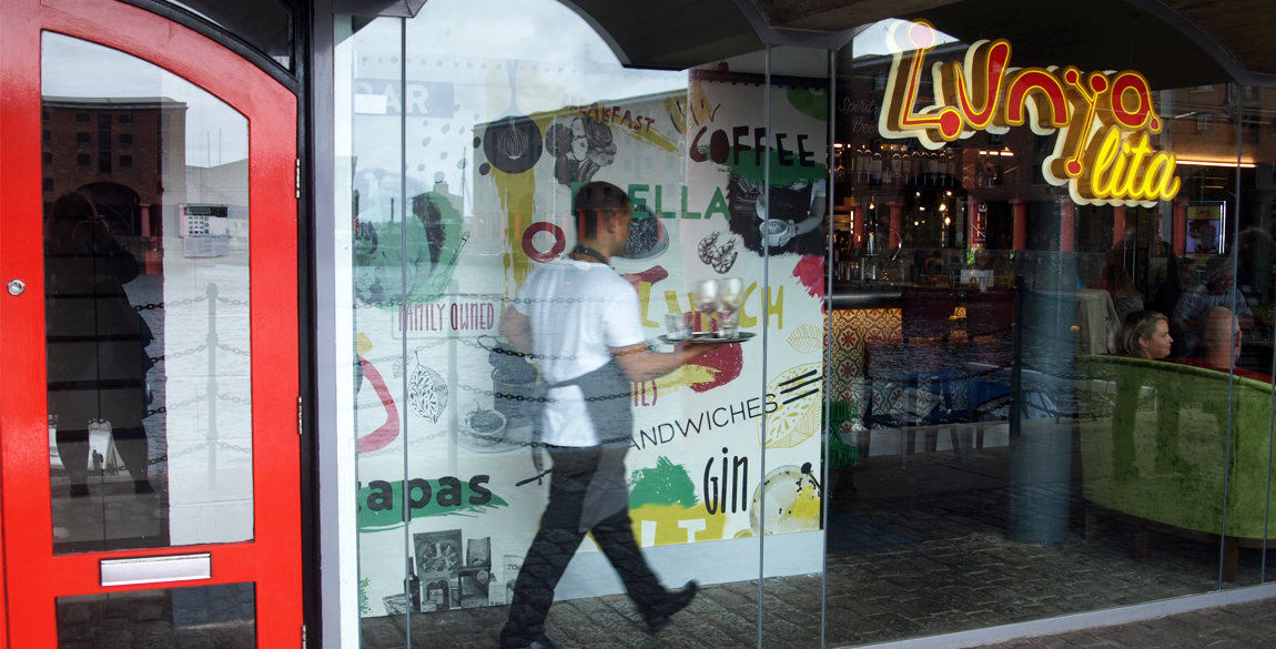 Exterior shot of restaurant with name on the glass and man walking past wall illustration on the inside