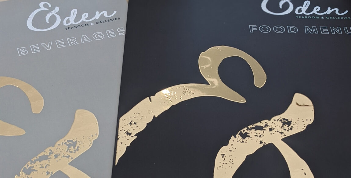 A photograph of the back of the Eden Tearoom Menus. A gold metallic ampersand sits on a coloured background.