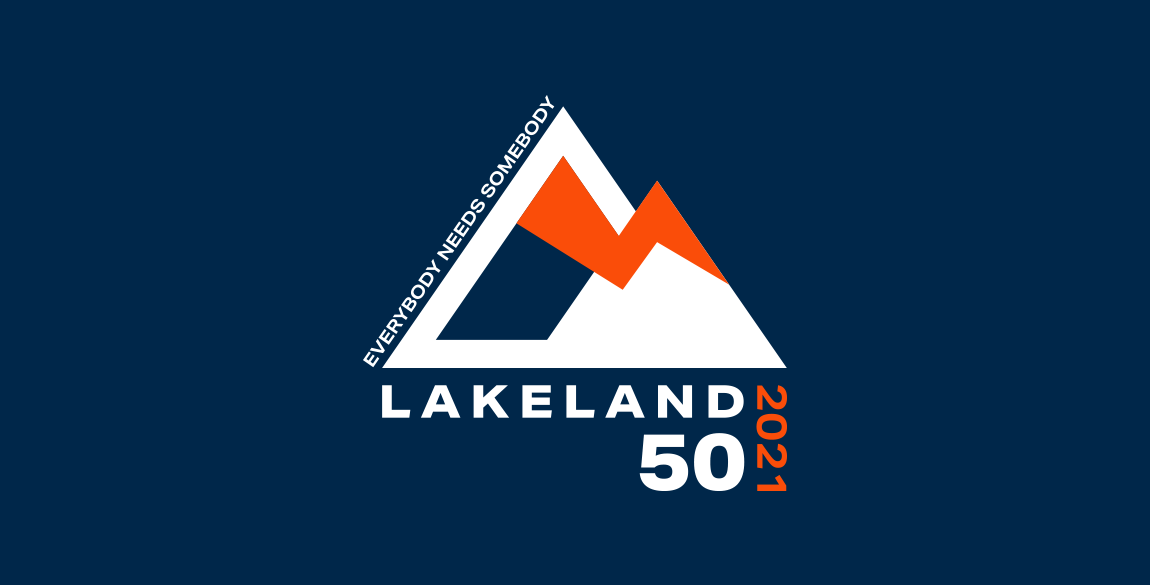 """Logo depicting two mountains, one slightly smaller than the other front. Lightening bolt joins the two. Text up the left of left mountain reads """"everybody needs somebody"""". Text below reads Lakeland 50 2021."""