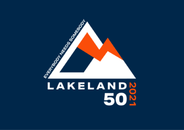 Image to show Lakeland 50 2021 logo design. Depicts mountains joined together by a thunderbolt. Text up left of left mountain says everybody needs somebody. Text underneath logo says Lakeland 50 2021.